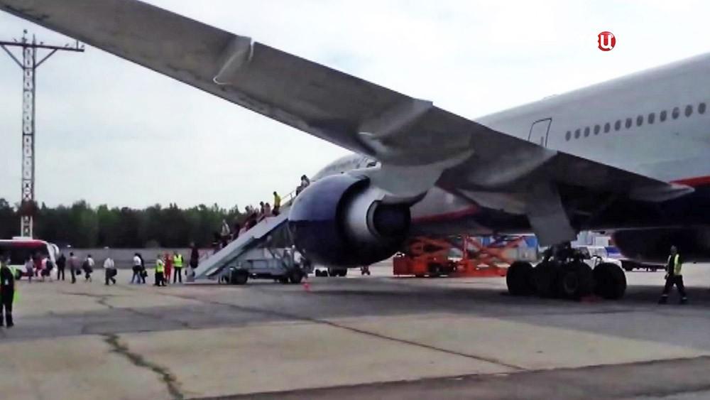 Пассажиры выходят из самолёта