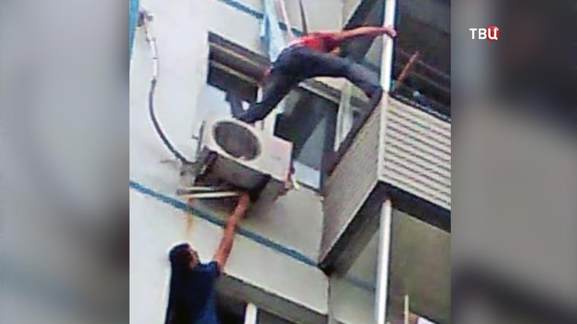 Люди спасают выпавшего из окна ребёнка