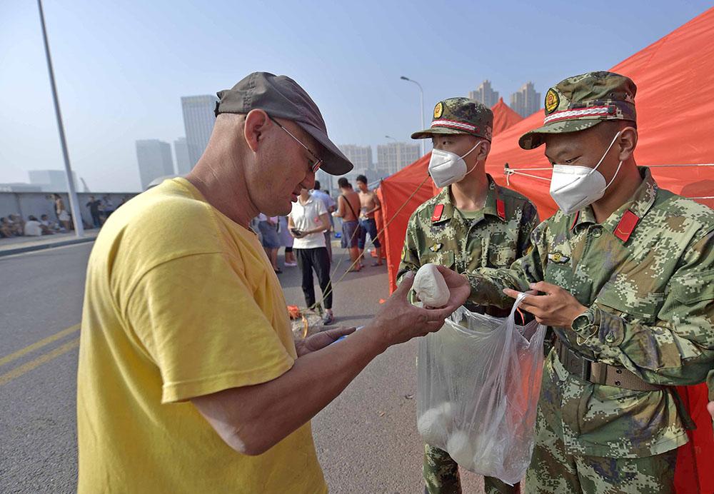 Китайские военные раздают жителям респираторы