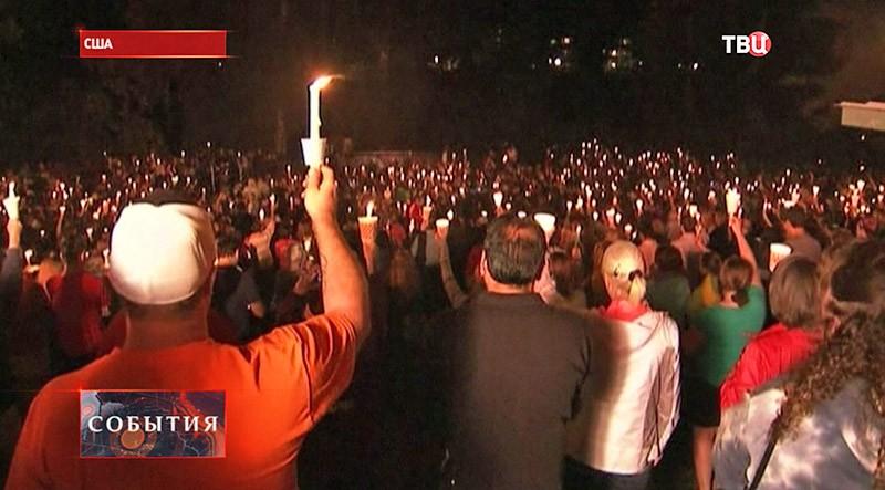 Люди поднимают свечи вверх в память о погибших