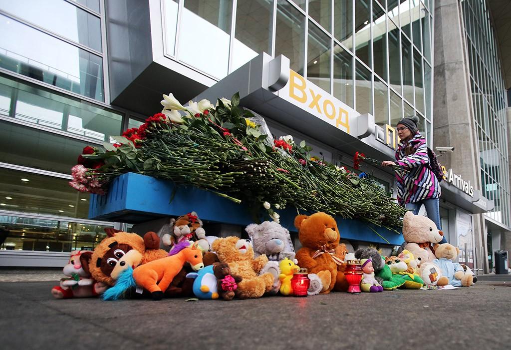 """Девушка возлагает цветы у входа в аэропорт """"Пулково"""""""