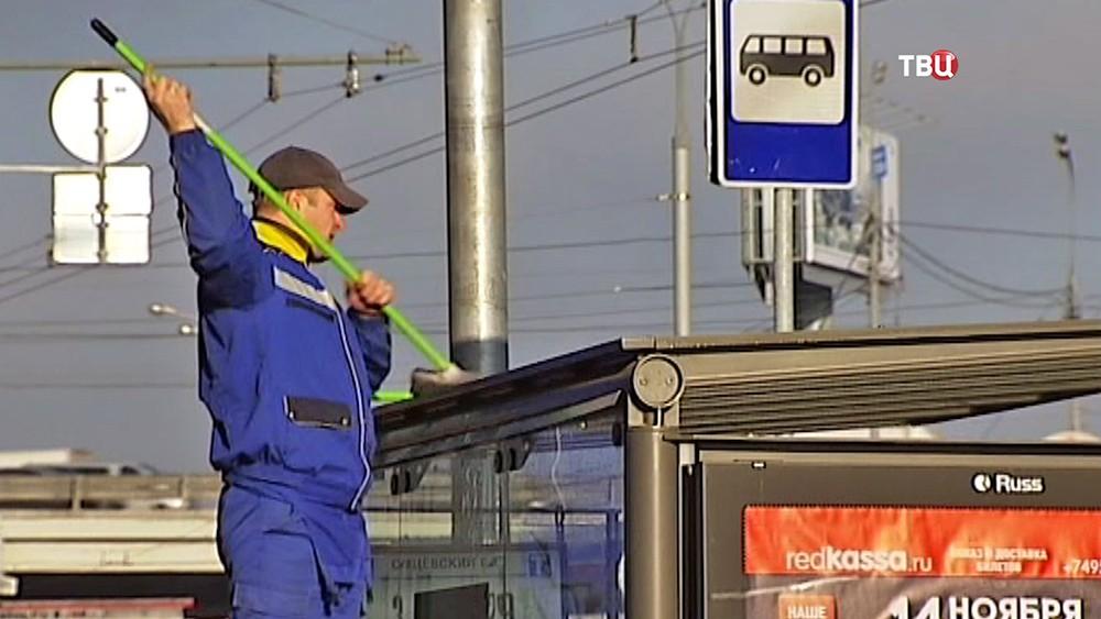 Коммунальщик чистит автобусную остановку