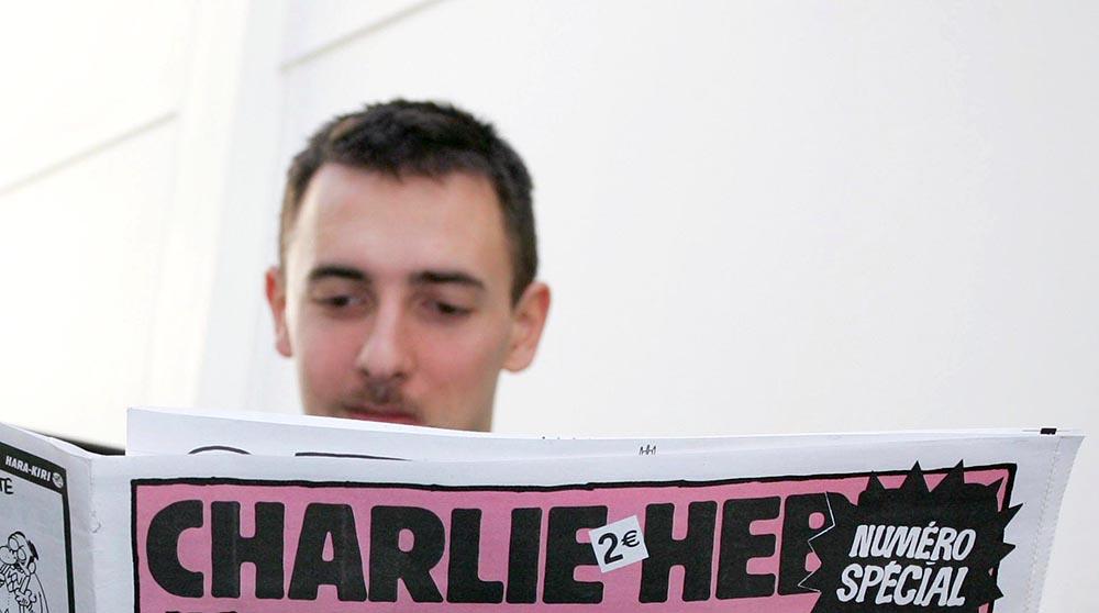 Мужчина читает Charlie Hebdo