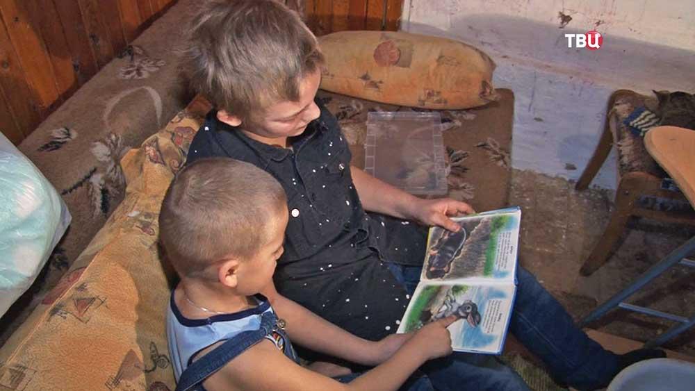 Подросток читают книгу своему брату