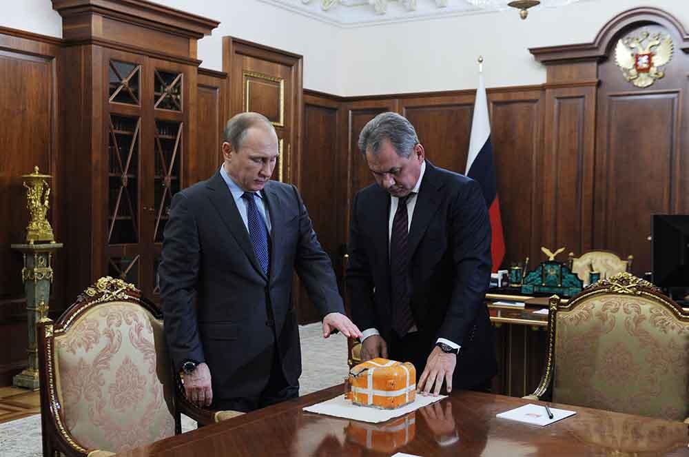 Президент России Владимир Путин и министр обороны России Сергей Шойгу осматривают параметрический самописец со сбитого Су-24