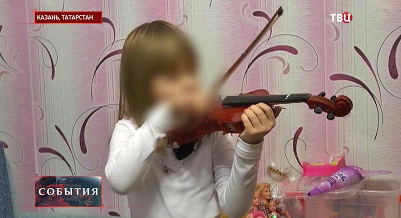 Девочка-инвалид играет на скрипке