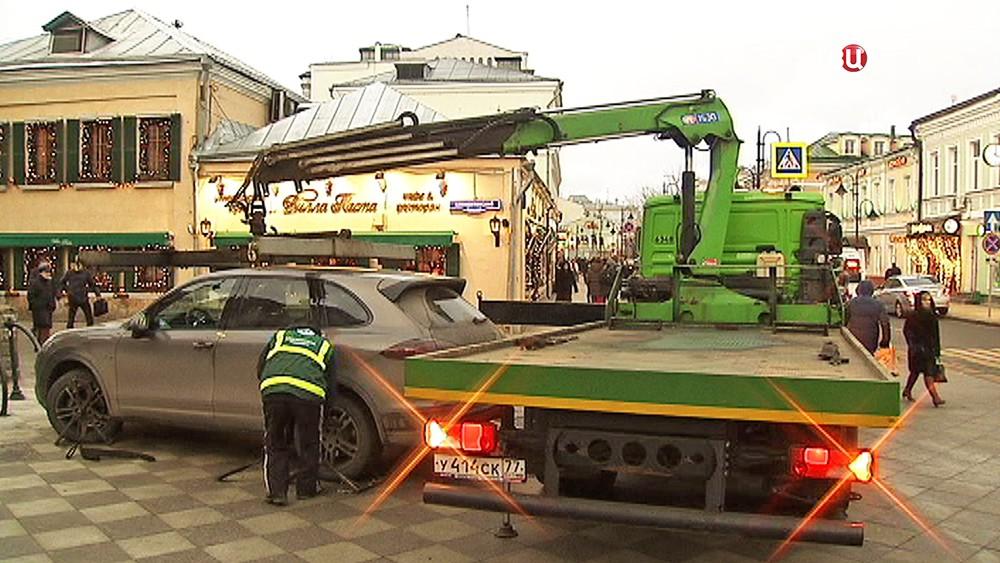 Эвакуатор поднимает автомобиль
