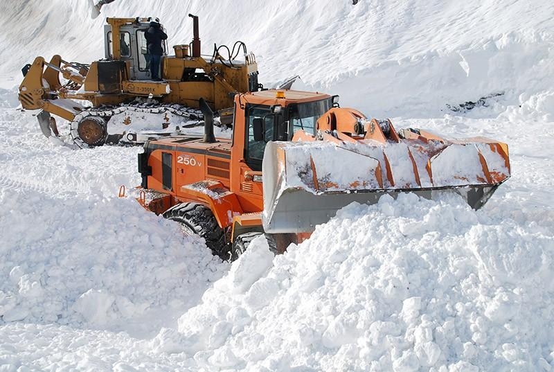 Сотрудники коммунальной службы проводят расчистку трассы после схода лавины