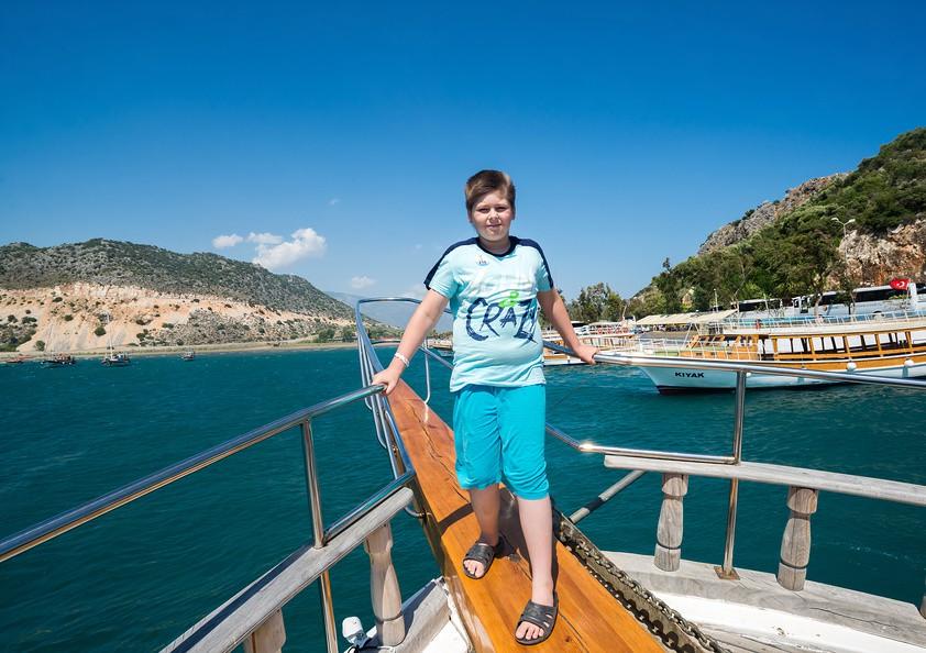 Мальчик стоит на яхте в Средиземном море около побережья Турции