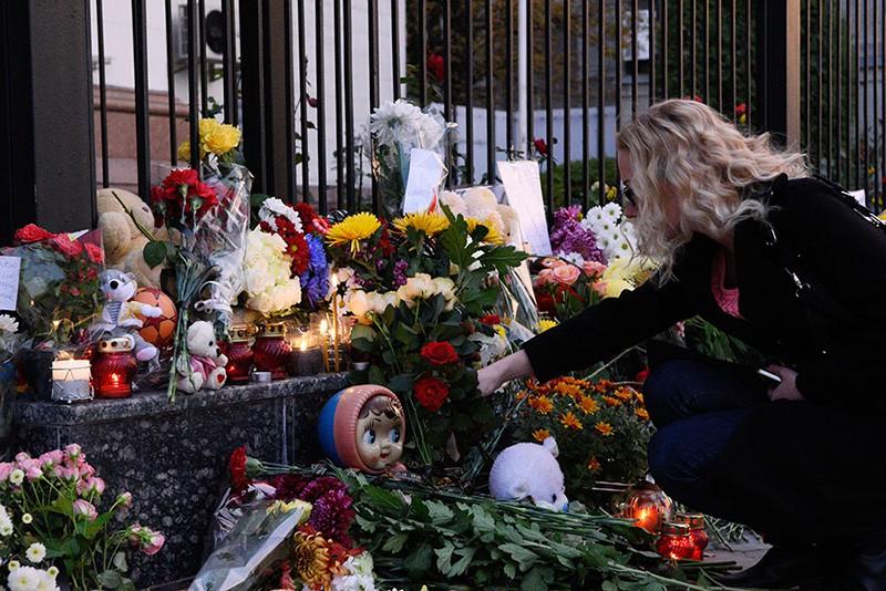 Женщина возлагает цветы в память о жертвах авиакатастрофы лайнера Airbus-321