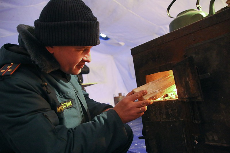 Сотрудник МЧС растапливает печь в мобильном пункте обогрева
