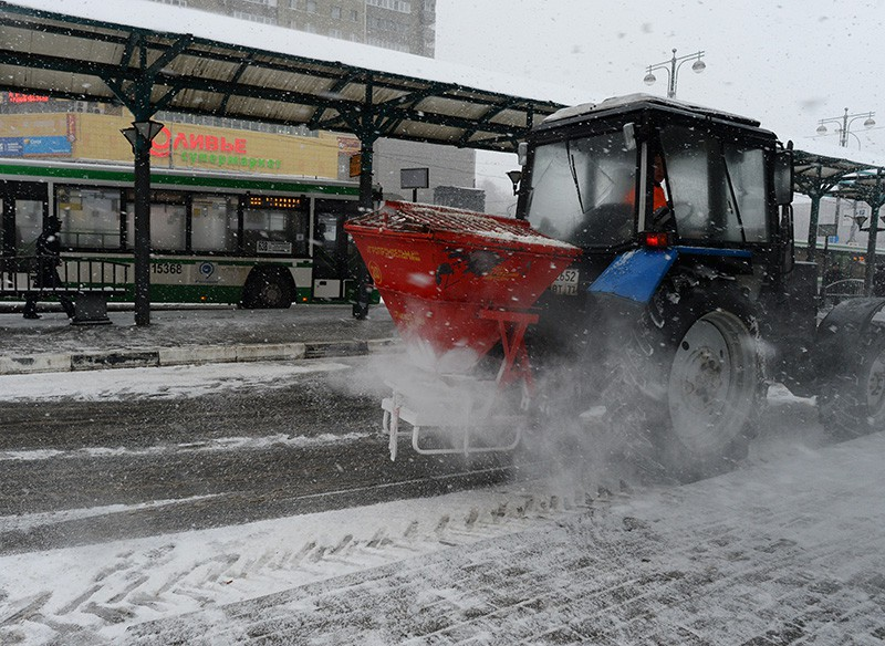 Трактор рассыпает на дорогу противогололедный реагент