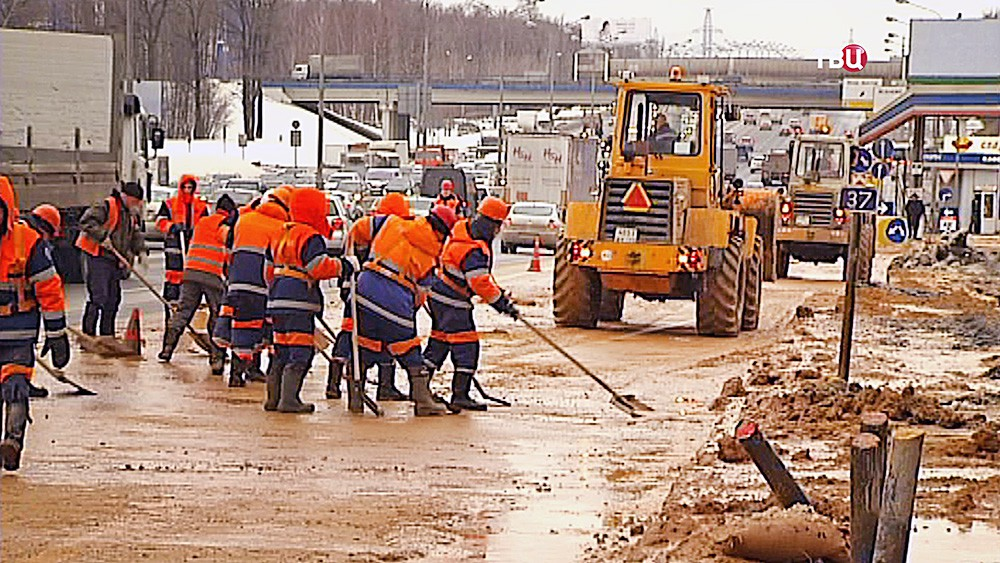 Работники дорожной службы устраняют последствия прорыва трубы