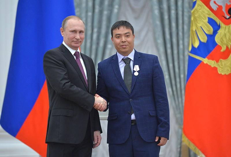 Президент России Владимир Путин и гражданин Киргизии Марат Исаев на церемонии вручения государственных наград и присвоения почетных званий