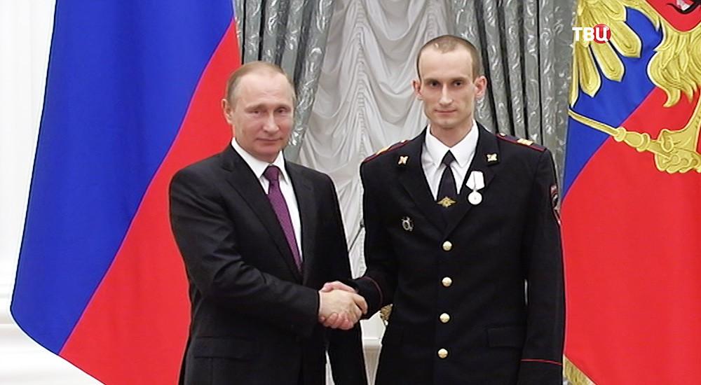 Президент России Владимир Путин и сержант полиции Артём Королюк на церемонии вручения государственных наград и присвоения почетных званий