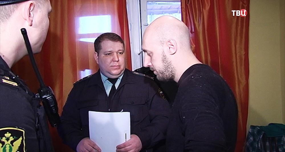 Житель квартиры, имеющий задолжность, беседует с судебным приставом