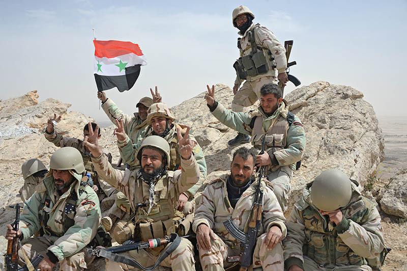 Бойцы отряда народного ополчения с флагом Сирии