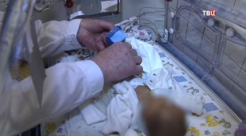 Врач осматривает новорожденную