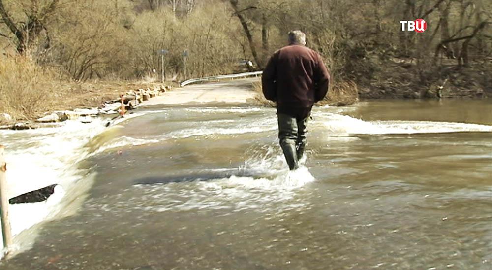 Мужчина переправляется через реку Осетр