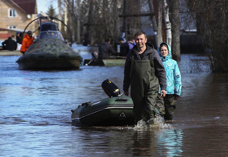Мужчина с лодкой во время паводка
