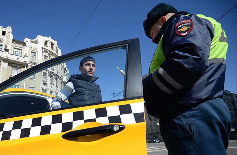 Сотрудник ГИБДД проверяет документы у водителя такси