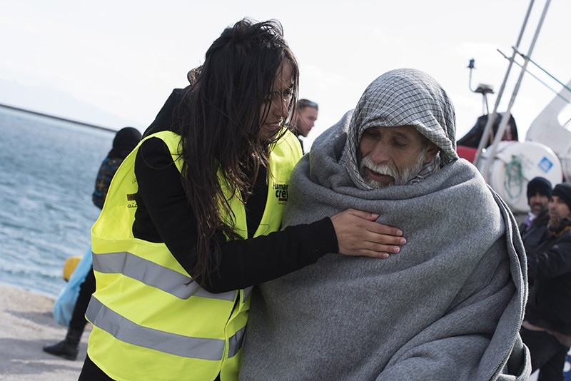 Спасатель оказывает помощь мигранту