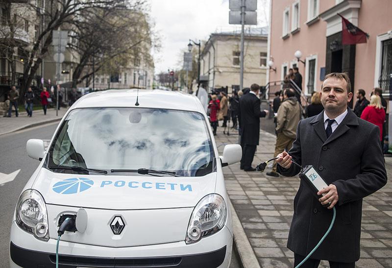 Водитель заряжает электромобиль