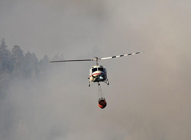 Вертолет во время тушения лесного пожара