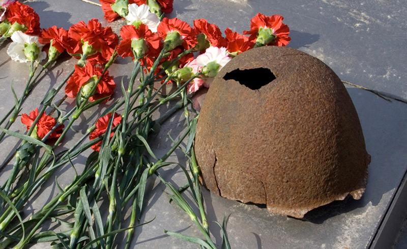 Солдатская каска и цветы на месте захоронения