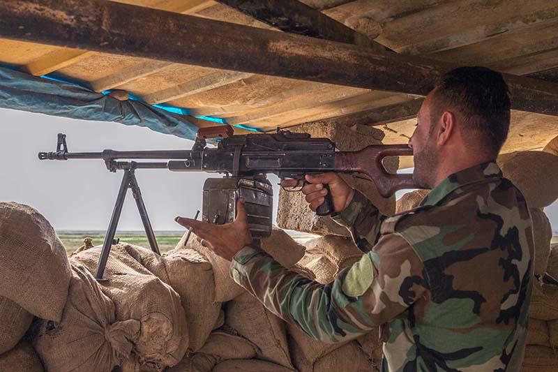 Солдат армии Ирака ведет прицельную стрельбу из пулемета