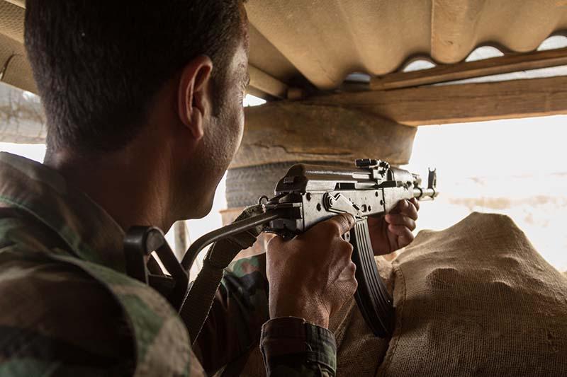 Солдат армии Ирака ведет прицельную стрельбу из автомата