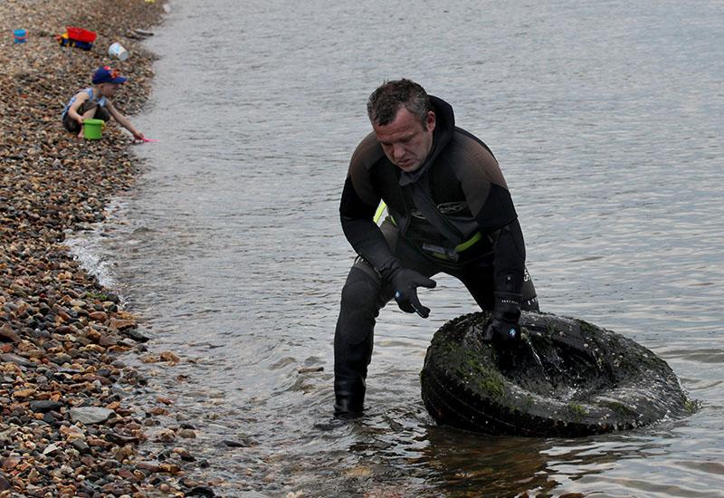 Дайвер очищает от мусора морское дно