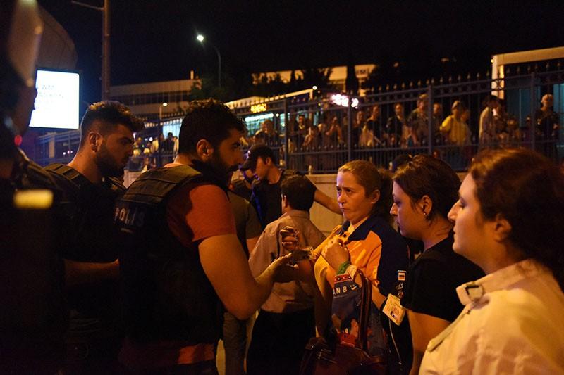 Полицейский общается с пассажирами в аэропорту Стамбула после теракта