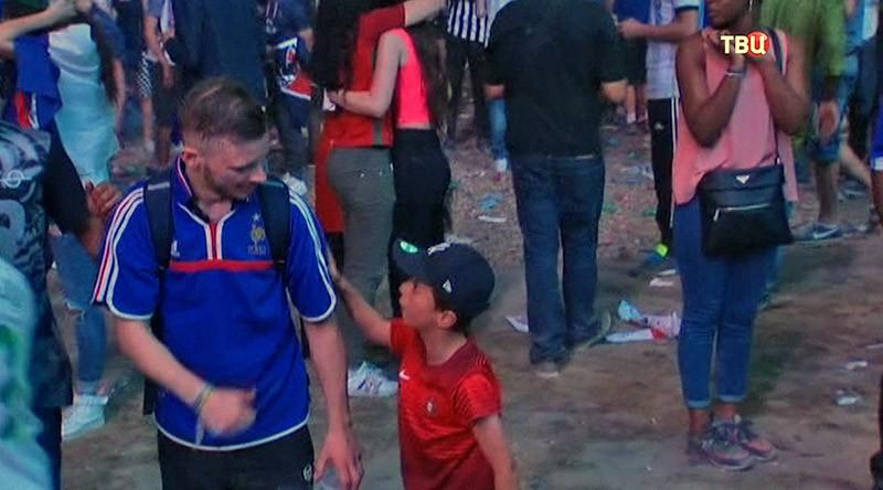Маленький португальский болельщик утешает плачущего француза
