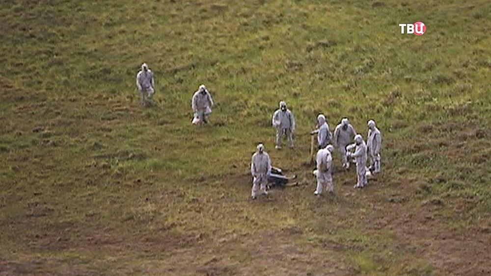 Специалисты в костюмах биозащиты на месте заражения
