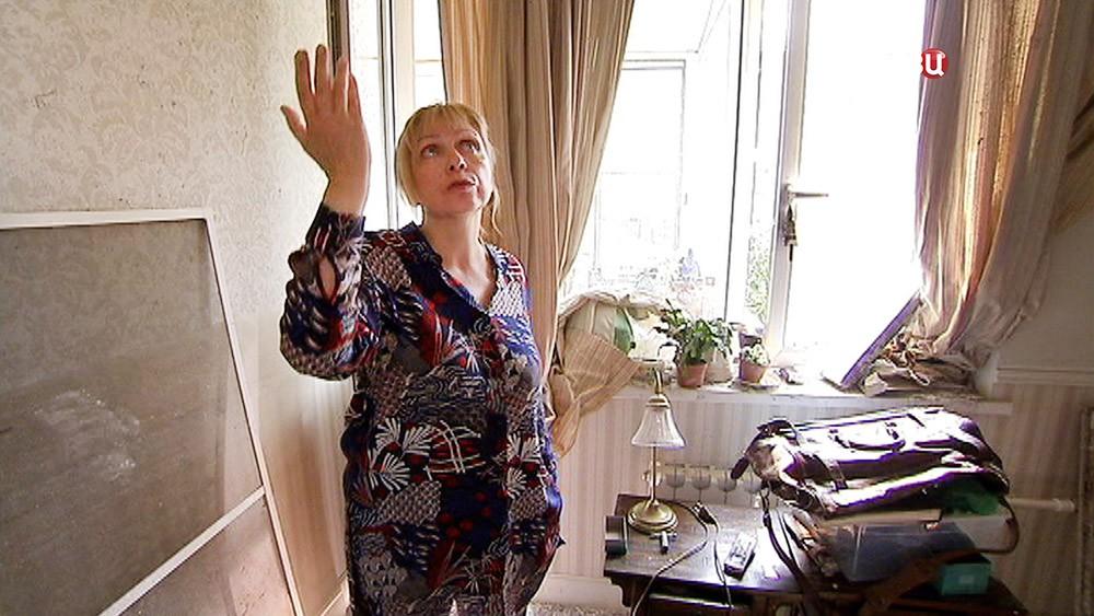 Женщина показывает последствия потопа в квартире