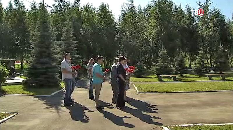 Люди несут цветы к памятнику