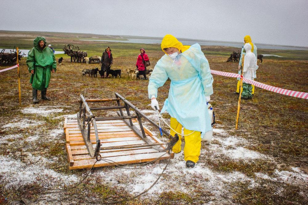 Специалисты в костюмах биозащиты работают с населением на месте заражения