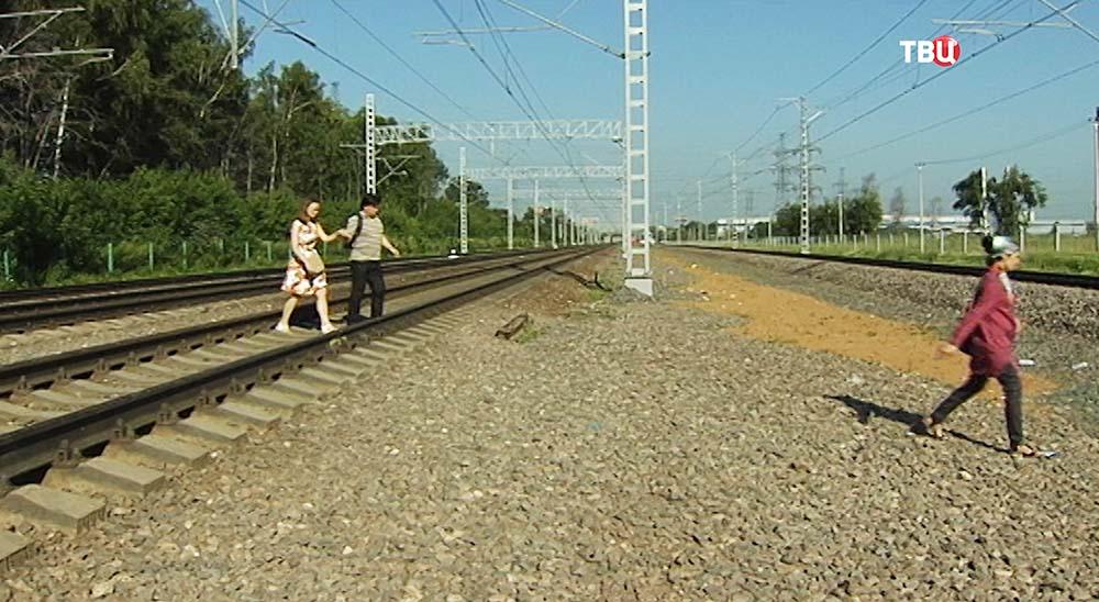 Люди переходят через железнодорожные пути