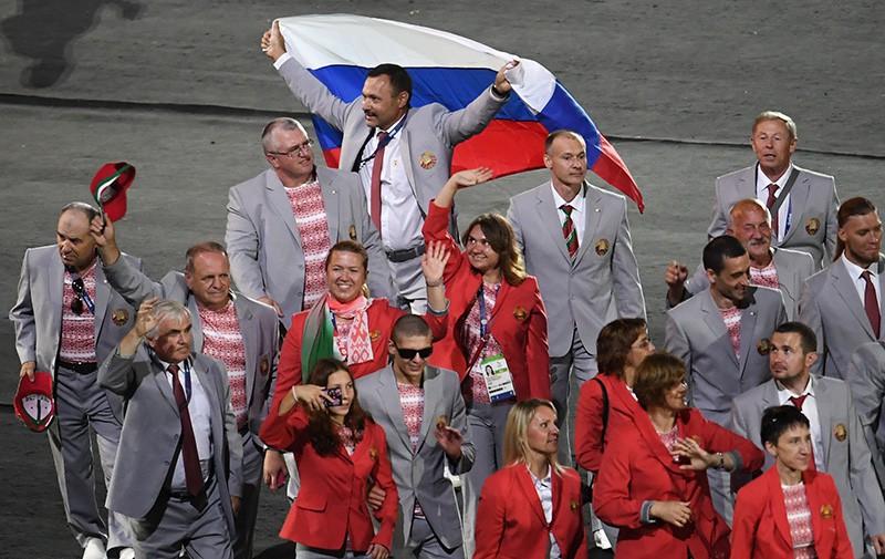 """Директор """"Республиканского центра олимпийской подготовки по легкой атлетике"""", представитель белорусской делегации Андрей Фомочкин с флагом России во время парада атлетов"""