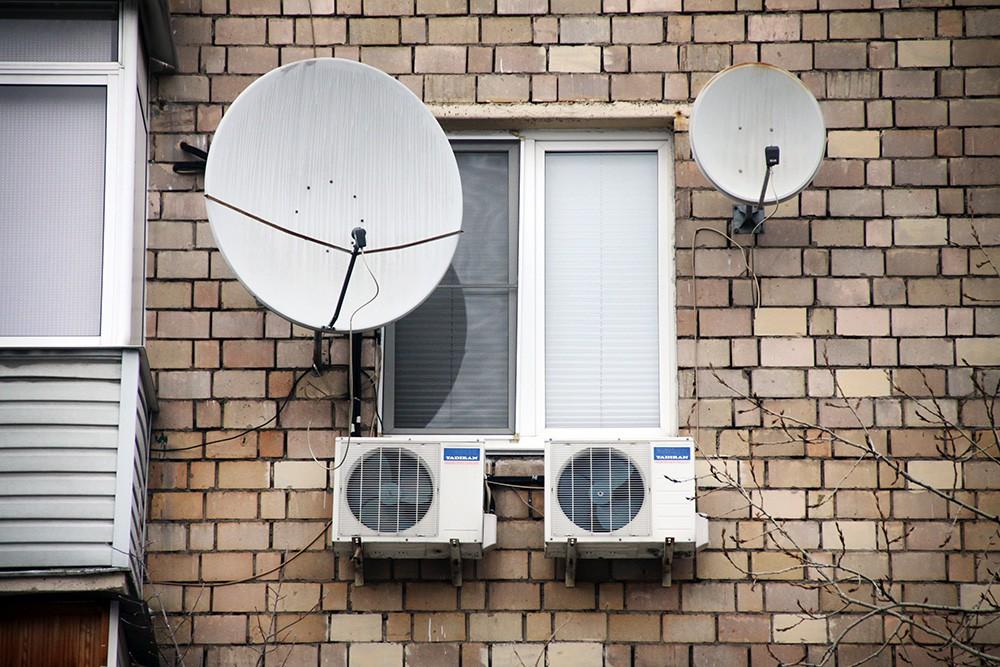 Кондиционеры и спутниковые тарелки на фасаде дома