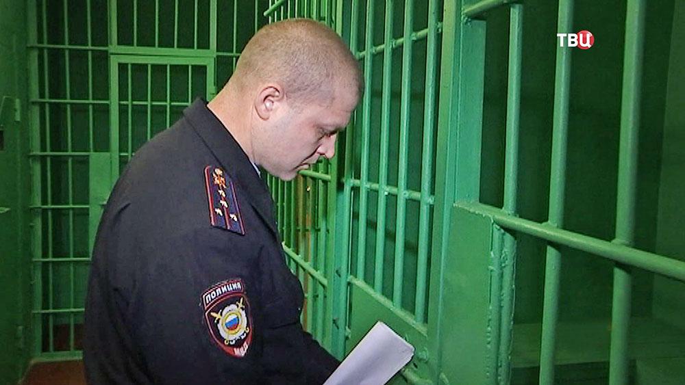 Полицейский привел задержанного в КПЗ