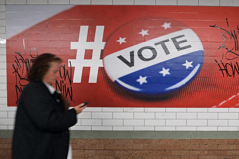Прохожая у плаката, посвященного голосованию на выборах президента США
