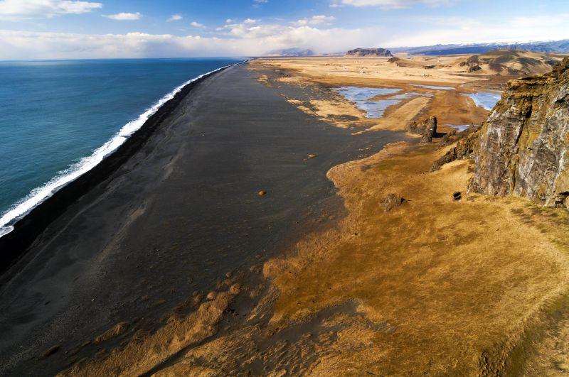 Черный песчаный пляж, возникший в результате разрушения вулканической породы