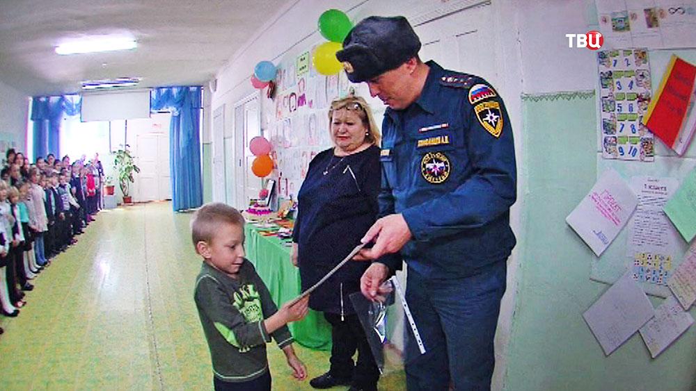 Сотрудник МЧС награждает семилетнего Антона Родина, спасшего брата и сестру из пожара