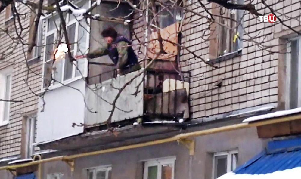 Мужчина бросает бутылки с коктейлем Молотова с балкона