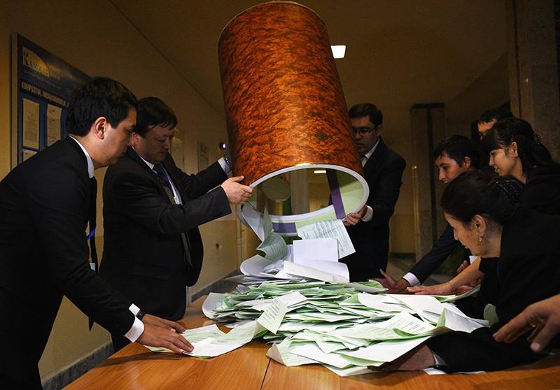 Выемка бюллетеней членами избирательной комиссии на избирательном участке во время выборов президента Узбекистана
