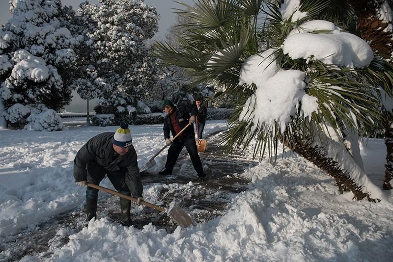 Мужчины расчищают от снега Приморскую набережную в Сочи