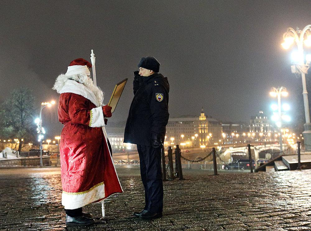 Дед Мороз с сотрудником полиции у фуры с главной новогодней елкой страны на Красной площади