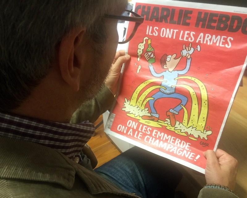 Мужчина читает выпуск Charlie Hebdo